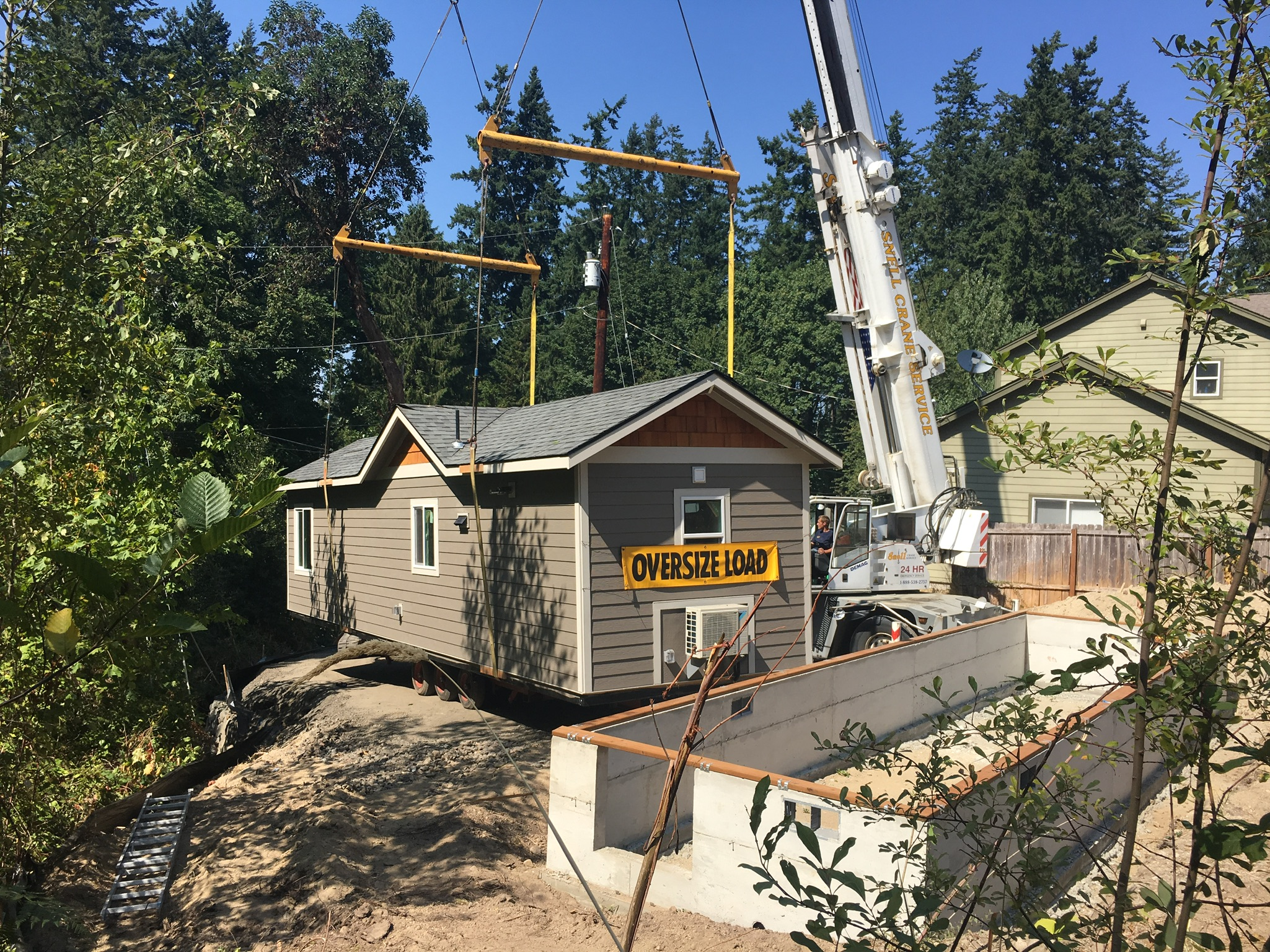 Backyard cottage being delivered to home by crane